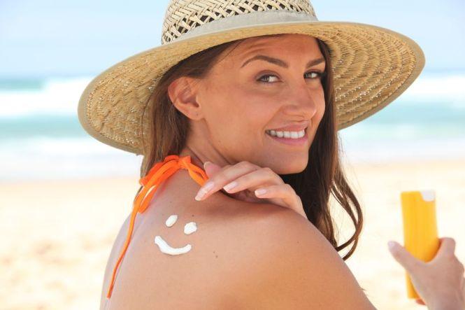 12019424 - woman applying suncream at the beach